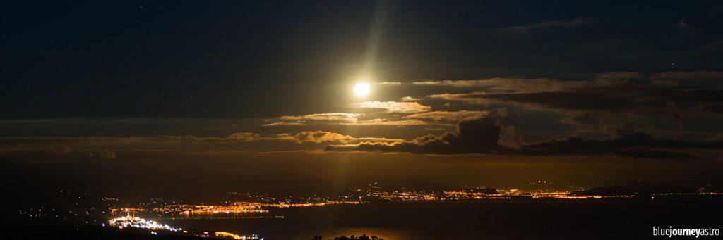 Fotografia notturna di un paesaggio illuminato dalla Luna al tramonto.